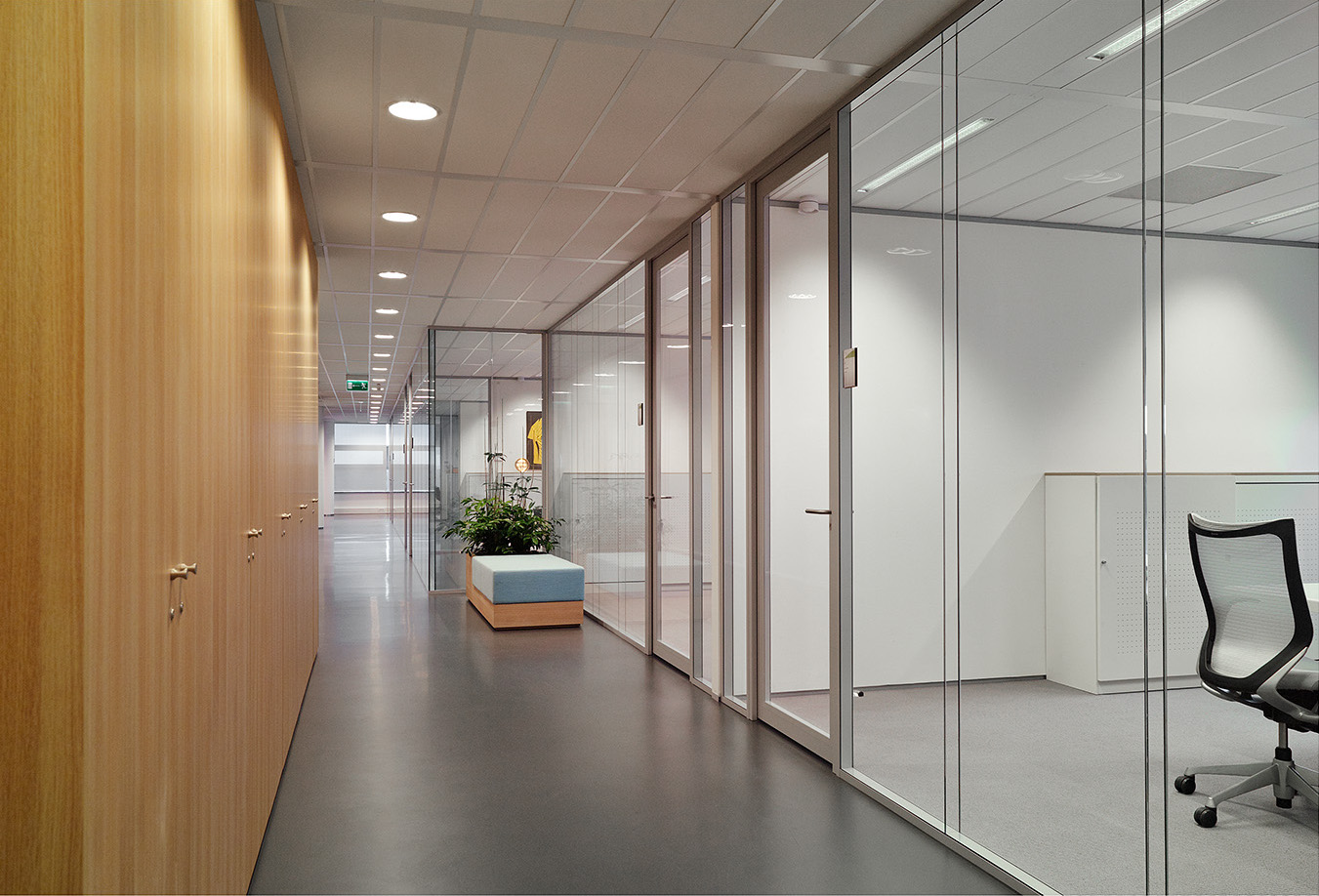 Corridor with on the right side IQ-Structural glass system wall with seamless panel joins.