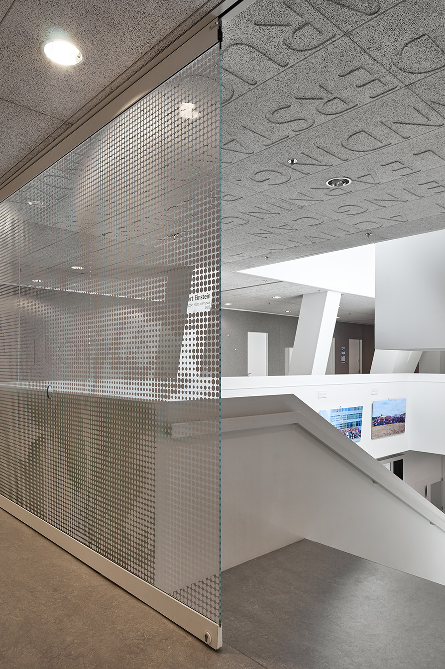 Full glass large sliding door at stair case at Leiden University College The Hague