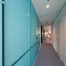 Corridor with a blue colored glass flush wall