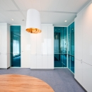 Blue glass flush partition wall with shades between the glass