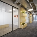 Corridor / office dividing partitions wall made of acoustic laminated single glass and a framed door.