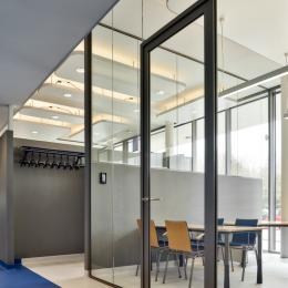Aluminum door and door frame fully surrounded by glass