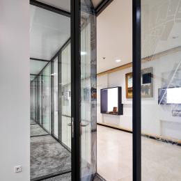 Glazensysteemwand met flush kaderdeur uitgevoerd in zwarte profielen