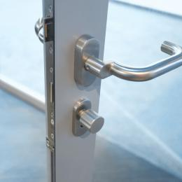 Lock and doorhandle in a fire resistant framed door EW30
