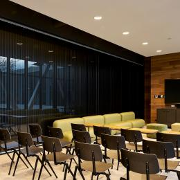 Within a meeting room with closed blinds inside the partition walls of QbiQ