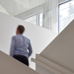 Man at staircase with glass at Leiden University College The Hague
