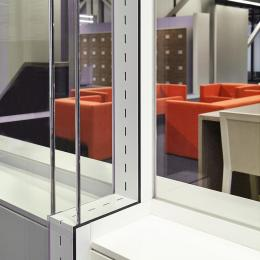 Double glass office wall with acoustic slots between the glass