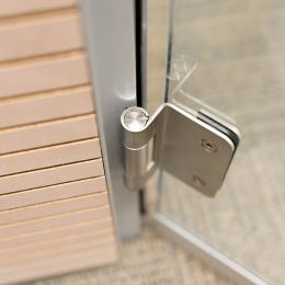 Detail of a stainless steel hinge of a DK42 door frame and a tampered glass door
