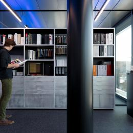 Glass partition with a bookcase in front at The Flow Houthavens Amsterdam