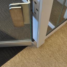 Drop seal under a tempered glass door
