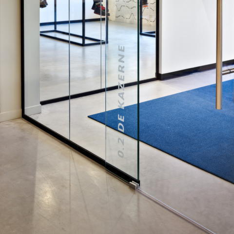 Detail of a glass sliding door in a glass partition wall system