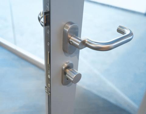 Lock and doorhandle in a fire resistant framed door EW30