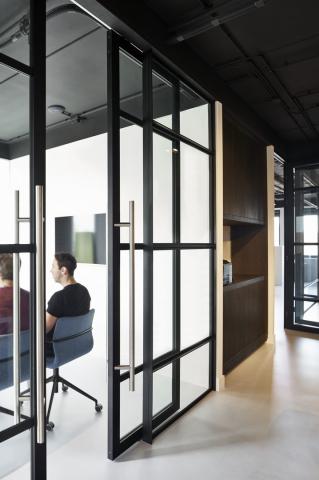Sliding door in a industrial look glass wall