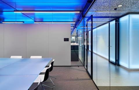Fire resistant glass partition, dividing two offices.
